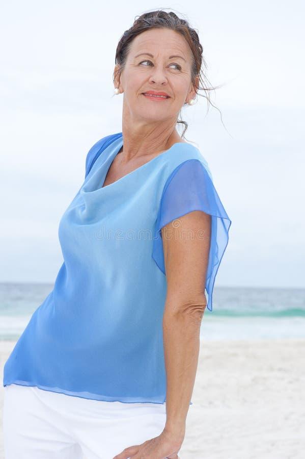 Den älskvärda ståenden mognar stranden för kvinnablåttblusen fotografering för bildbyråer