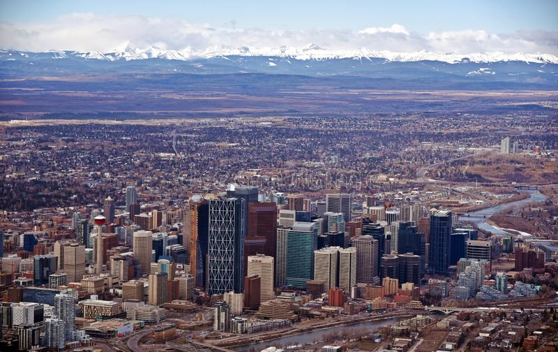 Den härliga staden av Calgary med snö täckte kanadensiska steniga berg i bakgrunden arkivbilder