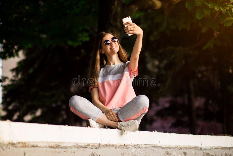 Den h?rliga stads- kvinnan i solglas?gon g?r selfiest?enden utomhus- i sommardag arkivfoto