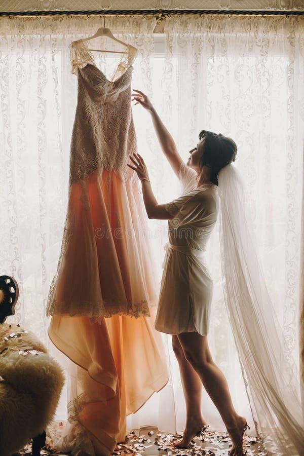 Den härliga stilfulla brunettbruden i siden- ämbetsdräkt och skyler länge att gå till hennes fantastiska bröllopsklänning i morgo arkivbilder