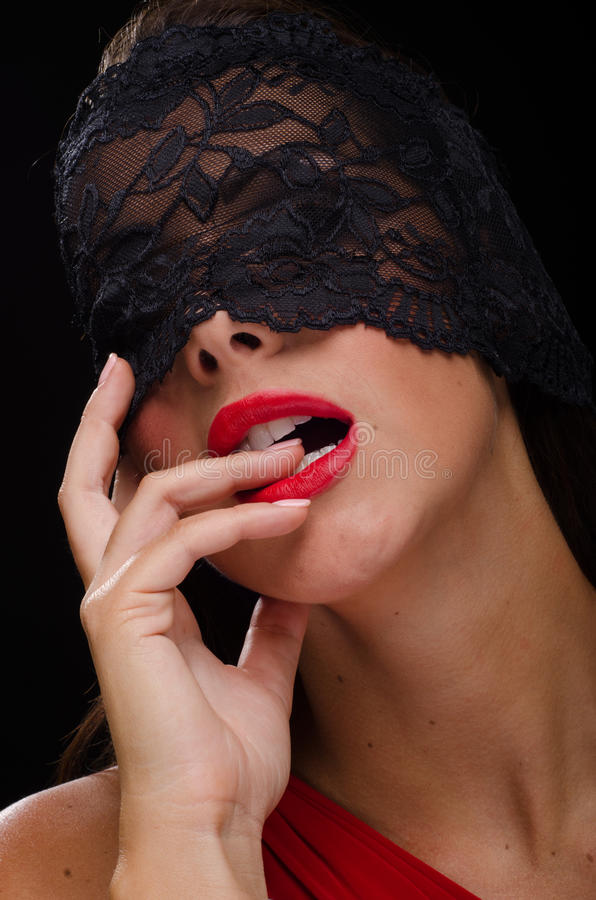 Den härliga stilfulla kvinnan som bär en svart, snör åt skyler och att le arkivfoton