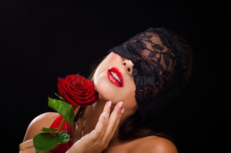 Den härliga stilfulla kvinnan som bär en svart, snör åt skyler och le på en ros royaltyfri foto