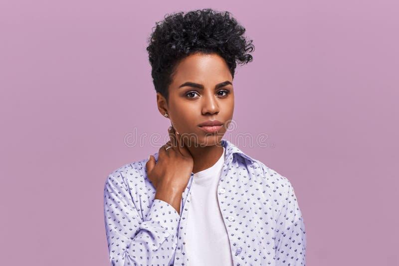 Den härliga stilfulla unga afrikansk amerikankvinnan med mörkt lockigt buskigt hår tycker om sommar vilar, har det allvarligt och fotografering för bildbyråer