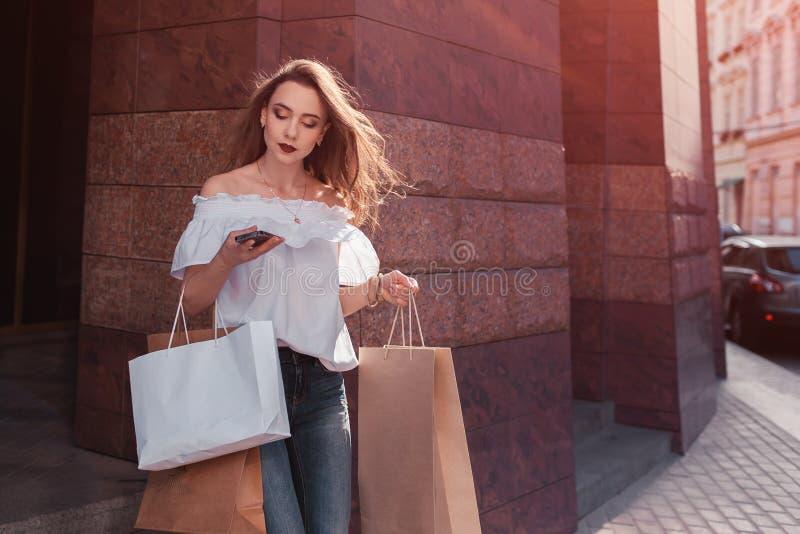 Den härliga stilfulla unga kvinnan med shoppingpåsar som går ut ur galleria och, mottar en appell royaltyfri fotografi
