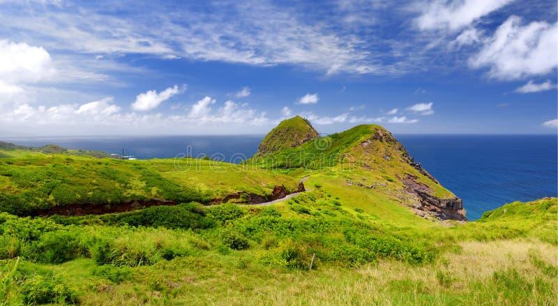 Den härliga stillsamma sikten av det Maui landskapet med vit fördunklar över gröna fält Maui Hawaii royaltyfria foton