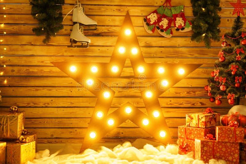 Den härliga stora stjärnan står mot väggen och glöder, den glödande juldekoren royaltyfri fotografi