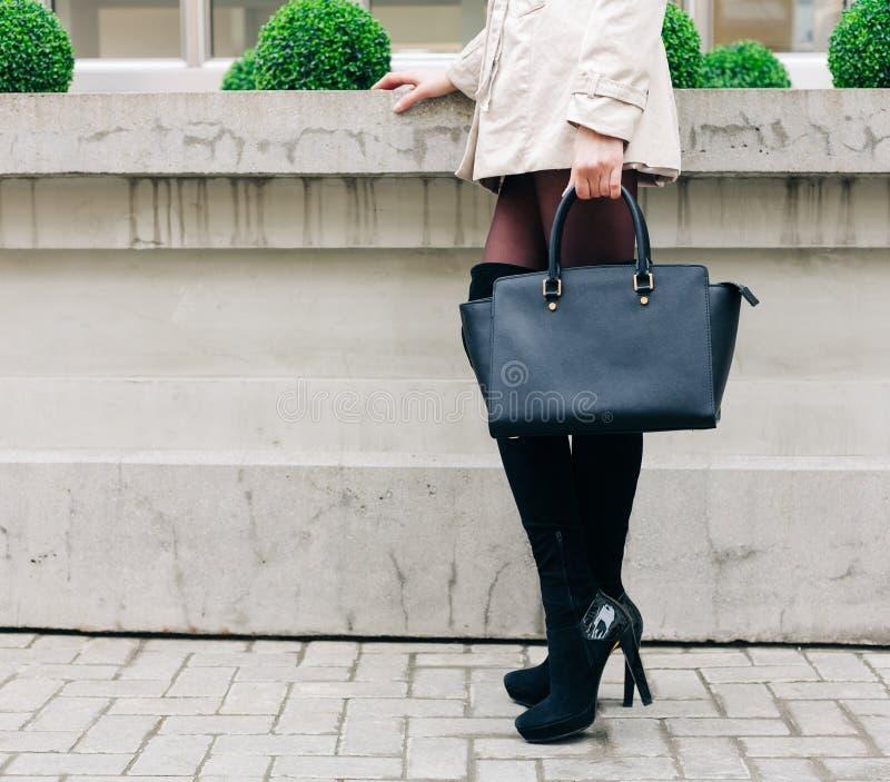 Den härliga stora svarta handväskan på armen av den oerhörda långbenta brunettflickan i en trendig grå färg klär och att posera arkivbild