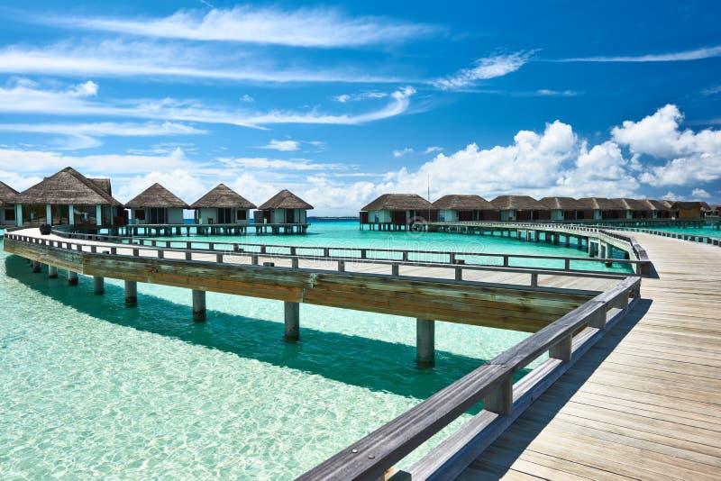 Den härliga stranden med bevattnar bungalower arkivfoton