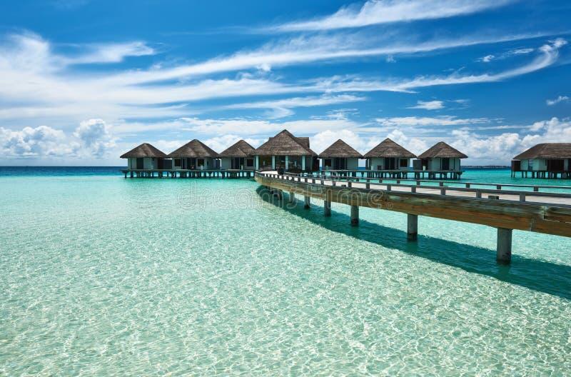 Den härliga stranden med bevattnar bungalower royaltyfri bild