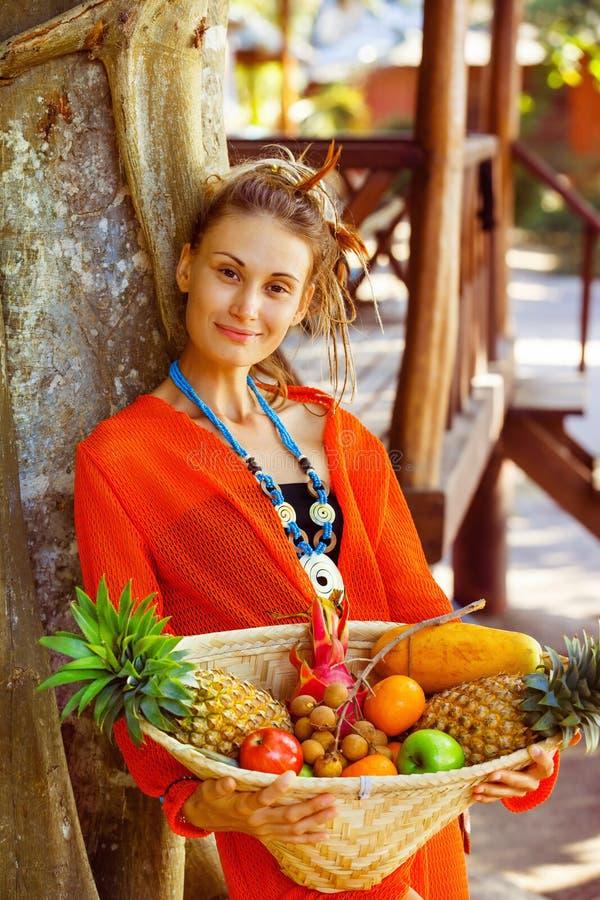 Den härliga sunda unga kvinnan är den hållande korgen av den tropiska fruien royaltyfri fotografi