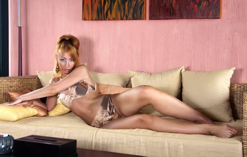 Den härliga suntanned unga kvinnan ligger i bikini på en soffa royaltyfri bild