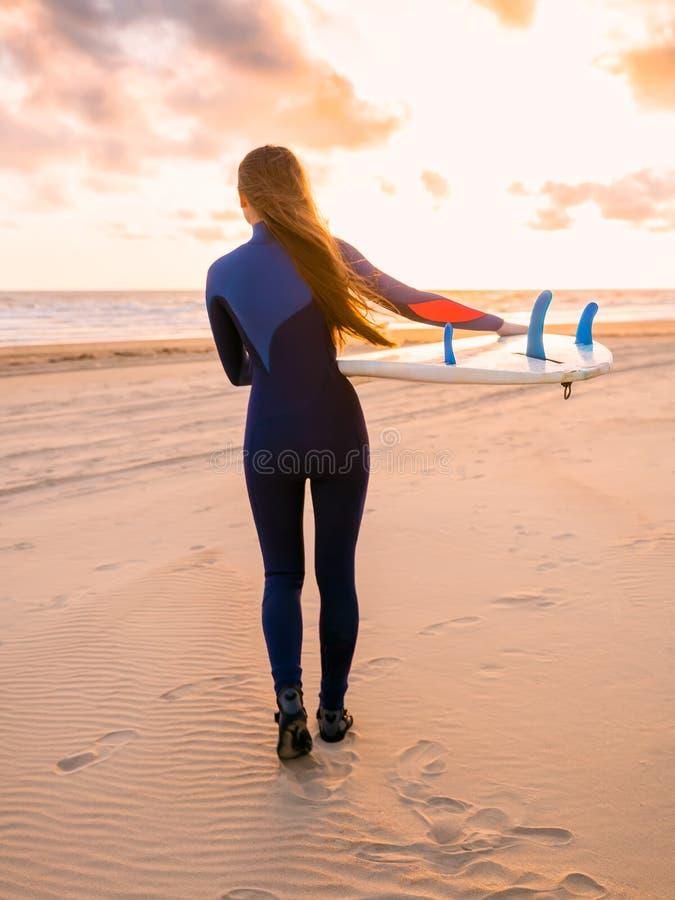 Den härliga surfareflickan för den unga kvinnan med surfingbrädan går till havet på en strand på solnedgången eller soluppgång arkivbilder