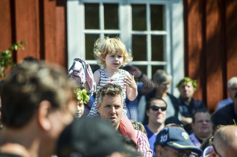 Den härliga svenska söta lyckliga kvinnan tycker om traditionell garnering av den mitt- sommardagen som bär den färgglade tjänstl royaltyfria foton