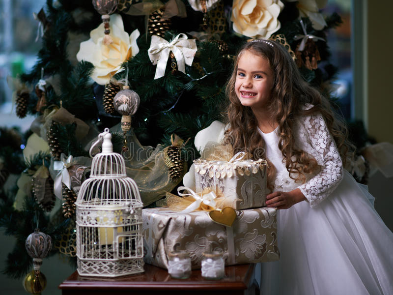 Den härliga tandlösa flickan i den vita klänningen tycker om gåvorna arkivfoton