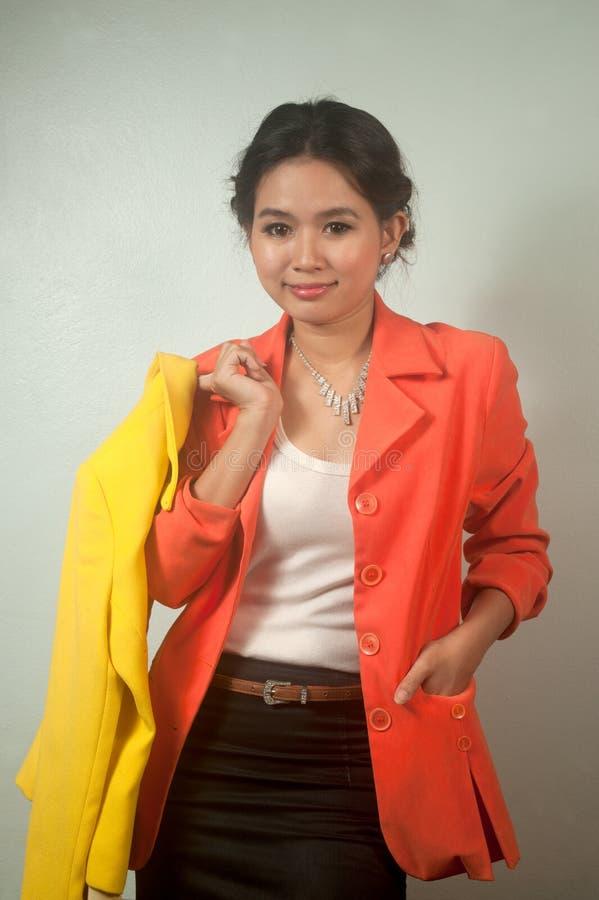 Den nätt asiatiska gulingen för affärskvinnainnehav passar. arkivbild