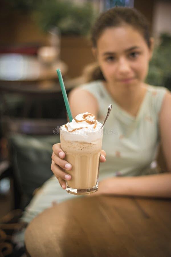 Den härliga tonåriga flickan att rymma ut hennes kaffe med mjölkar och piskad kräm i ett högväxt exponeringsglas royaltyfri bild