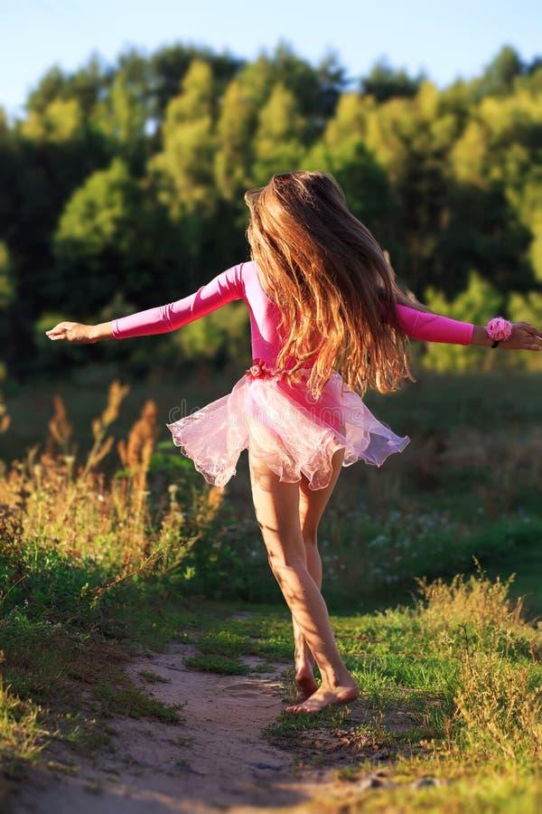 Den härliga tonåriga flickan dansar utanför på sommarsolnedgången arkivbilder