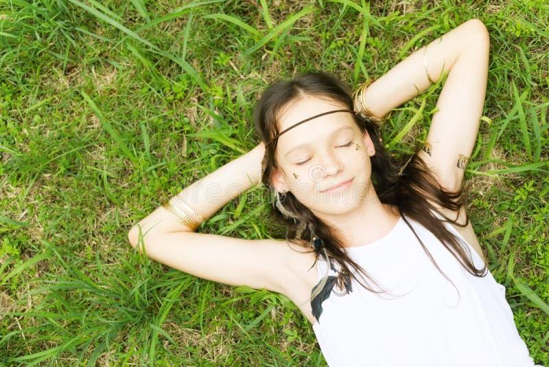 Den härliga tonåriga flickan i den vita klänningen som ligger på grönt gräs som ler, ögon stängde sig Top beskådar Boho stilståen arkivfoton