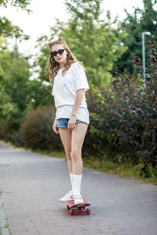 Den härliga tonåriga flickan som rider ett skridskobräde i, parkerar Begreppet av livsstilen, fritid arkivbild