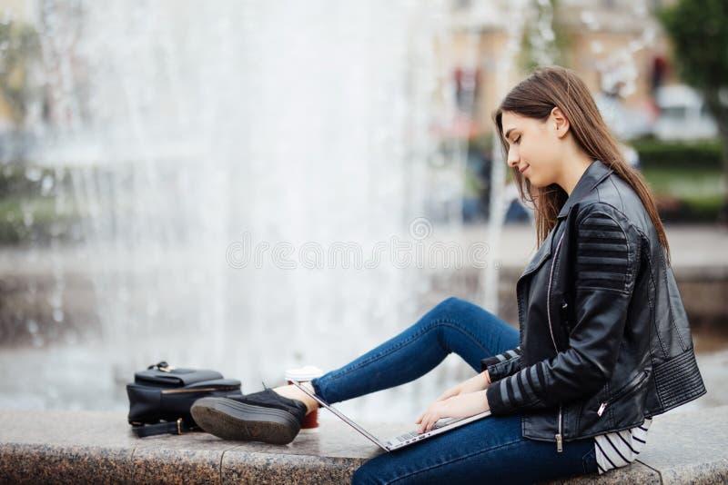 Den härliga tonåriga kvinnan använder hennes bärbar datordator utanför, medan sitta vid en springbrunn i en stadfyrkant royaltyfri bild