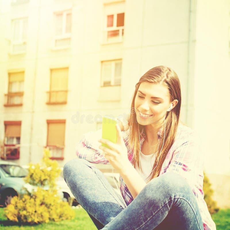 Den härliga tonårs- flickan parkerar in med den smarta telefonen som lyssnar till musik arkivbild