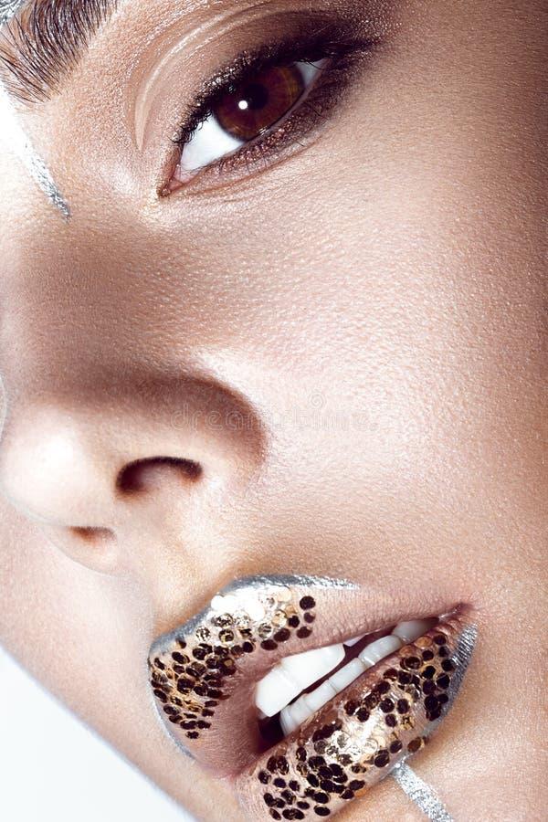 Den härliga trendiga flickan med idérikt blänker makeup och mousserar på kanter Slut upp skönhetframsida royaltyfri fotografi