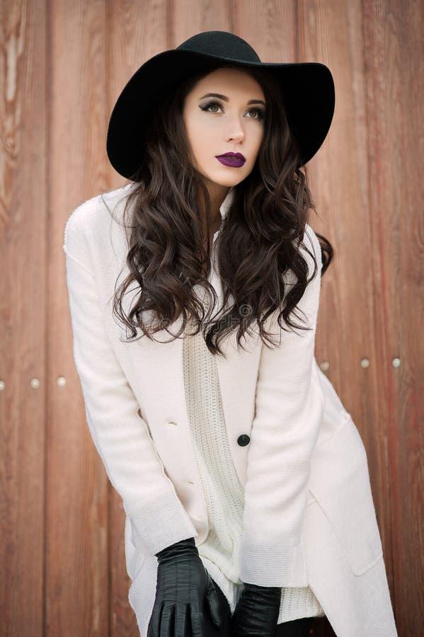 Den härliga trendiga le kvinnan i en svart hatt och vit täcker att posera utomhus nära porten royaltyfria bilder