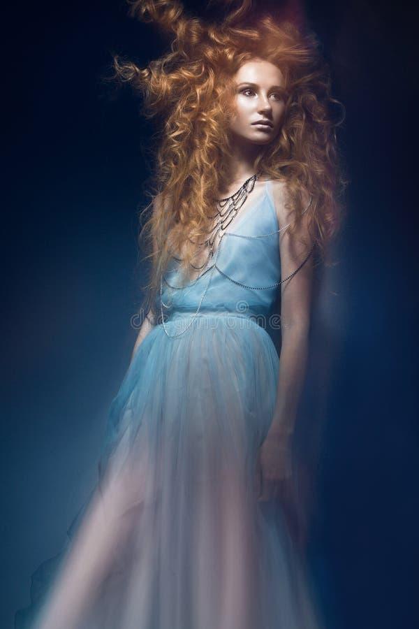 Den härliga trendiga rödhåriga flickan i den genomskinliga klänningen, sjöjungfrubild med den idérika frisyren krullar Modeskönhe arkivbild