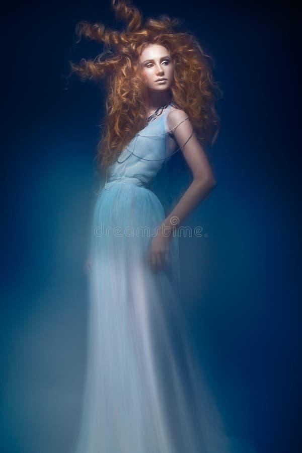 Den härliga trendiga rödhåriga flickan i den genomskinliga klänningen, sjöjungfrubild med den idérika frisyren krullar Modeskönhe arkivbilder