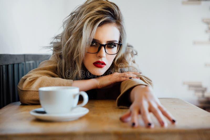 Den härliga trendiga stilfulla flickan sitter i ett kafé med en kopp kaffe royaltyfria bilder