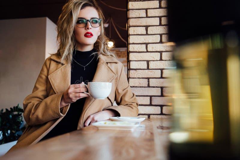 Den härliga trendiga stilfulla flickan sitter i ett kafé med en kopp kaffe royaltyfria foton