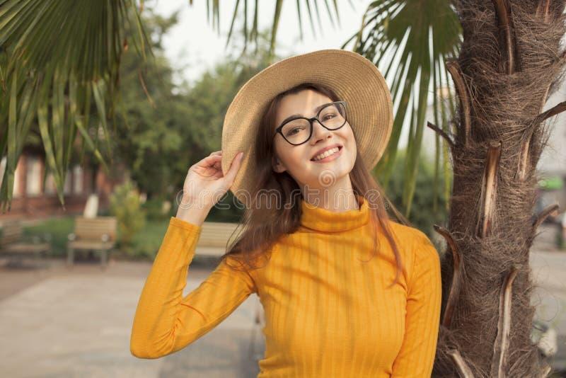 Den härliga trendiga unga kvinnan som ler i, parkerar, den gula överkanten, jeans, gymnastikskor, hatt royaltyfria bilder