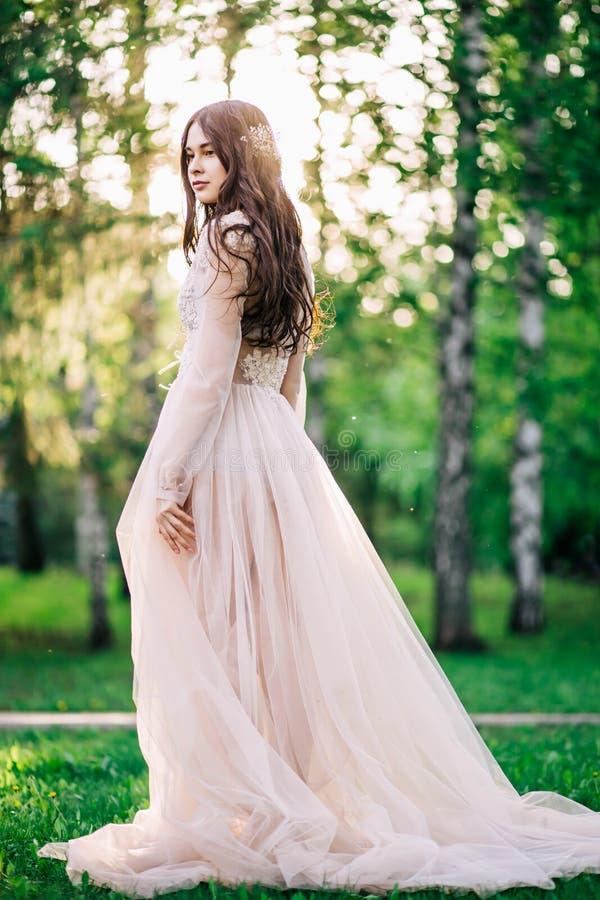Den härliga ung flickabrudbrunetten i delikat brud- budoarkappa av snör åt, och tyllen i beige färg är utomhus, i en parkera med  arkivbilder