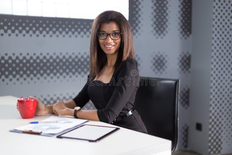 Den härliga unga affärsdamen i svart starkt följe sitter på kontorstabellen, rymmer den röda koppen royaltyfri bild