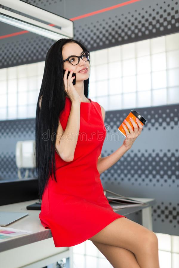 Den härliga unga affärskvinnan i röd klänning och exponeringsglas sitter på tabellen i kontors- och hållcoffekoppen royaltyfria bilder