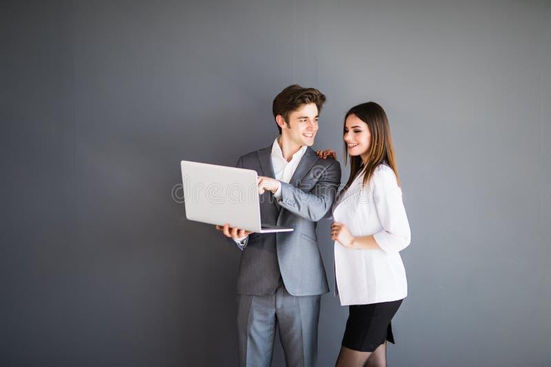 Den härliga unga affärskvinnan och den stiliga affärsmannen i formella dräkter använder en bärbar dator, samtal och att le som st arkivfoto