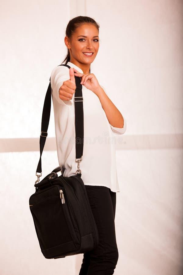 Den härliga unga affärskvinnan visar upp tummen som gesten för framgång royaltyfri fotografi