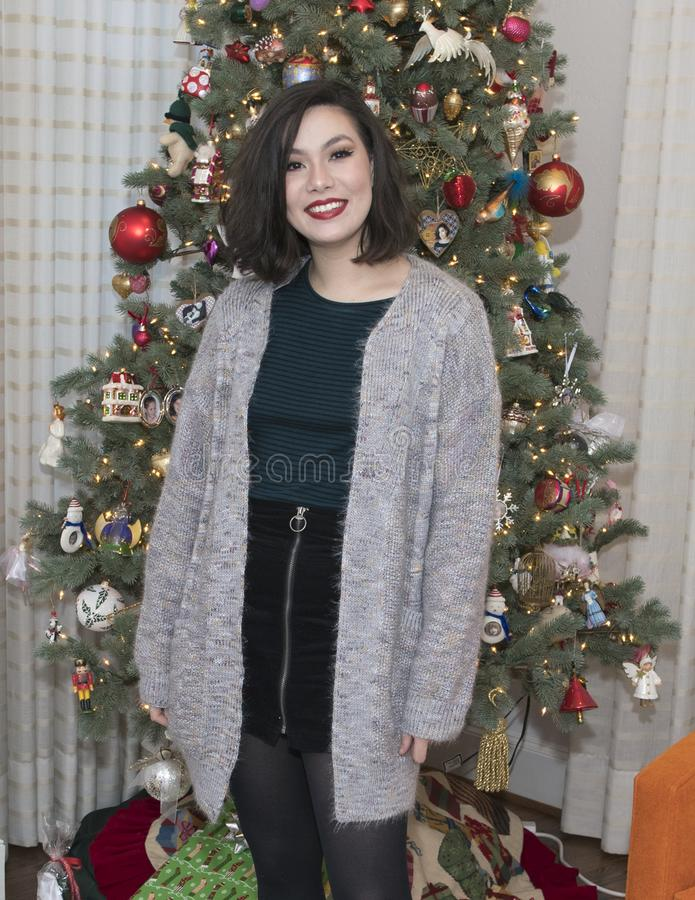 Den härliga unga Amerasian kvinnan poserade framme av en julgran arkivbild