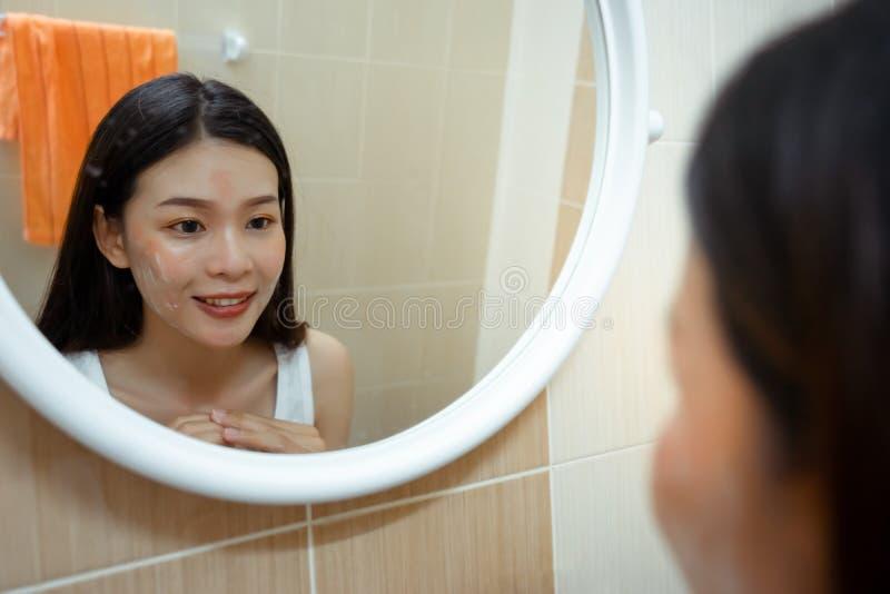 Den härliga unga asiatiska kvinnaframsidan tvättar sig med ansikts- skum royaltyfria bilder