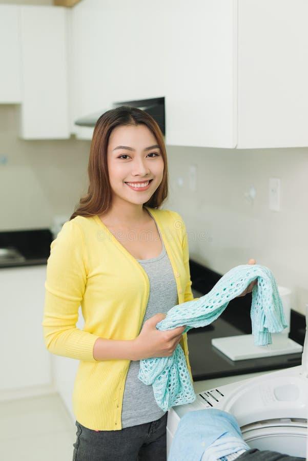 Den härliga unga asiatiska kvinnan rymmer en handfat med tvätterit, royaltyfri fotografi