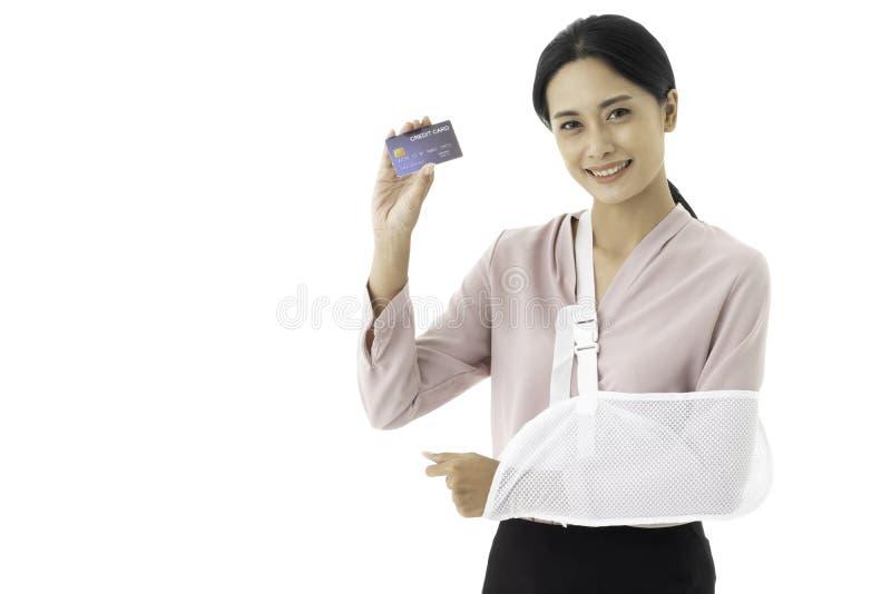 Den härliga unga asiatiska kvinnan såras med en bruten arm och en pålagd armrem royaltyfri fotografi