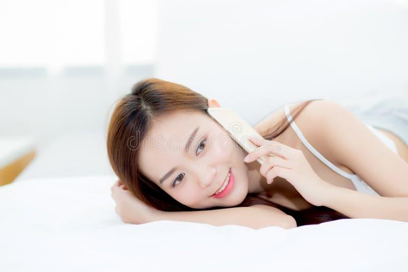 Den härliga unga asiatiska kvinnan som ler att ligga och, kopplar av på sängen i morgonen, flickan som använder mobilen som smart arkivfoto