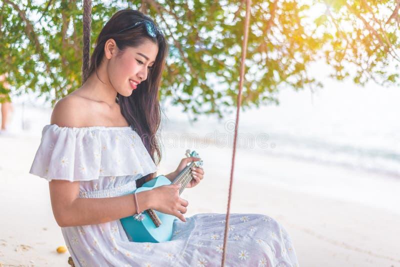 Den härliga unga asiatiska kvinnan som spelar med ukulelet och, kopplar av på th royaltyfria foton
