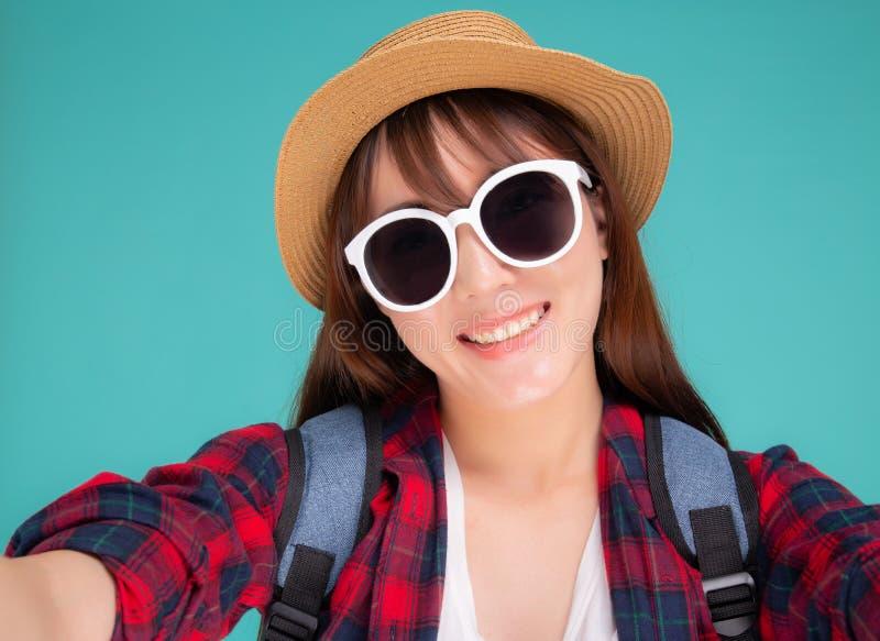Den härliga unga asiatiska kvinnan som tar selfie med kameran för, kopplar av i semester som isoleras på blå bakgrund arkivfoto
