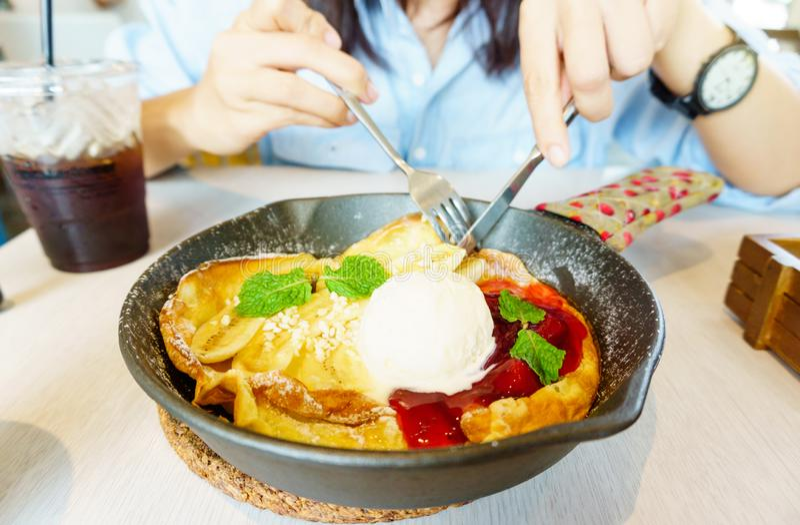 Den härliga unga asiatiska kvinnan tycker om att äta hemlagade fruktpannkakor med bananen, jordgubben, glass och med is kaffe Läc royaltyfri bild