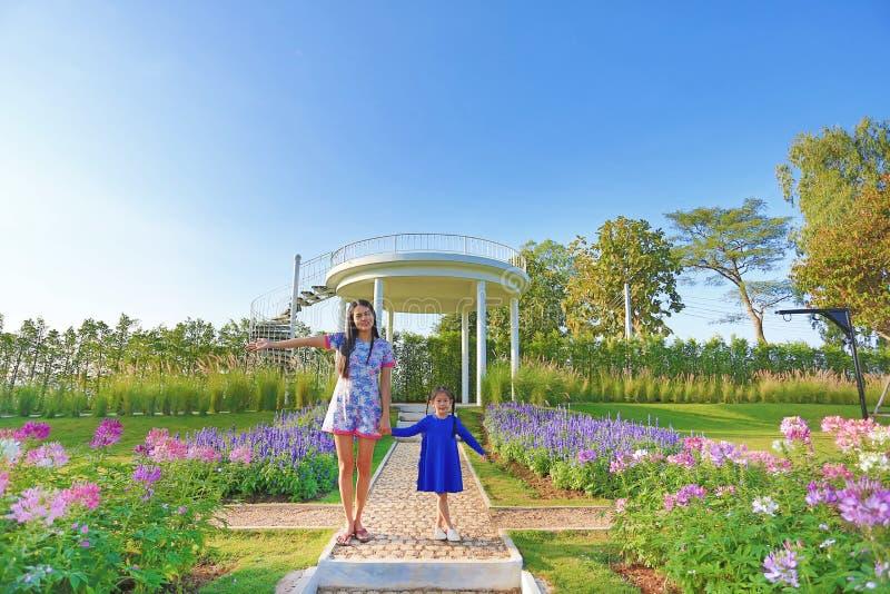 Den härliga unga asiatiska mamman med hennes dotter kopplar av i blommaträdgård royaltyfria bilder