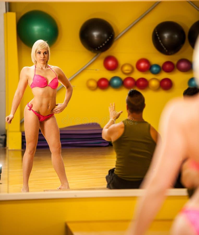 Den härliga unga bikinikonditionkonkurrenten utbildar att posera för t royaltyfria bilder