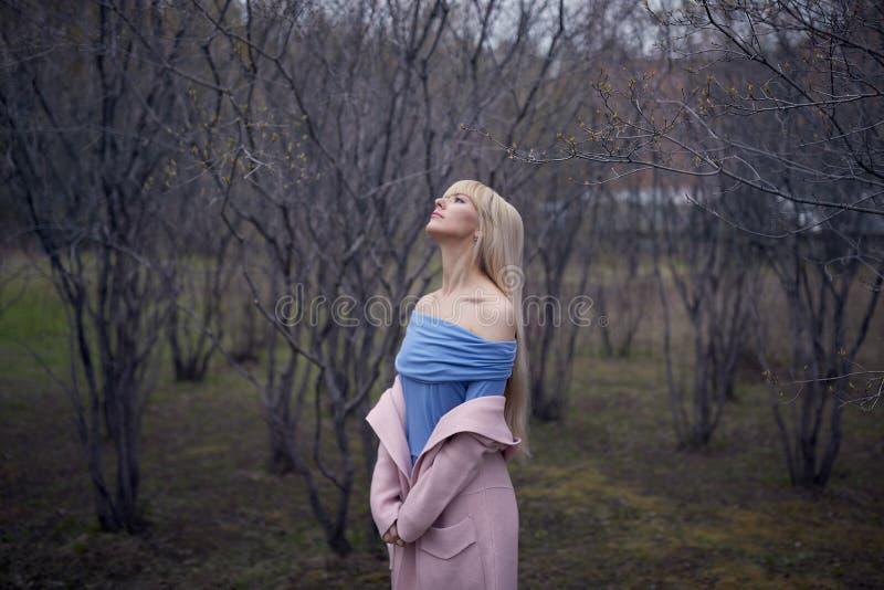 Den härliga unga blonda kvinnan går i parkera arkivfoto