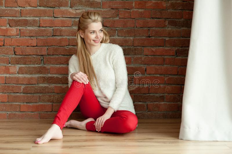 Den härliga unga blonda kvinnan i ett vitt värme omslaget, och röd zhdinsah, sitter på golvet nära fönstret, mot en vägg för röd  arkivfoton