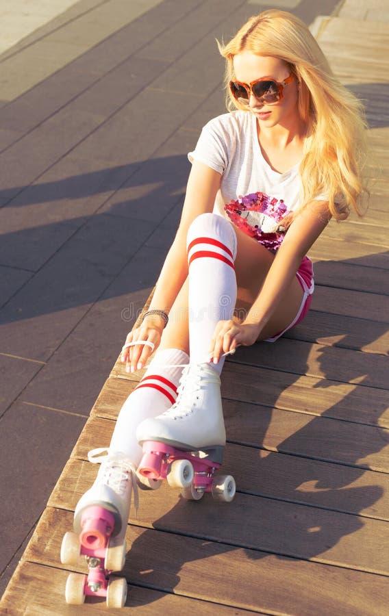 Den härliga unga blonda kvinnan i kortslutningar för sportar för en överkant rosa och tappningrullderby sitter på en bänk på en v royaltyfria foton